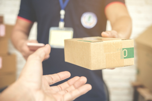 delivery-man-smiling-holding-cardboard-box_1150-8869-d1e06799